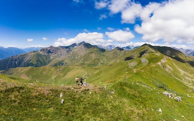 Antenne: paar rucksacktouristen, die auf berggipfeln wandern, landschaftlich reizvolle landschaft. sommerabenteuer auf den alpen. erfolg erobern reifer erwachsener mit spaß wohlbefinden fitness