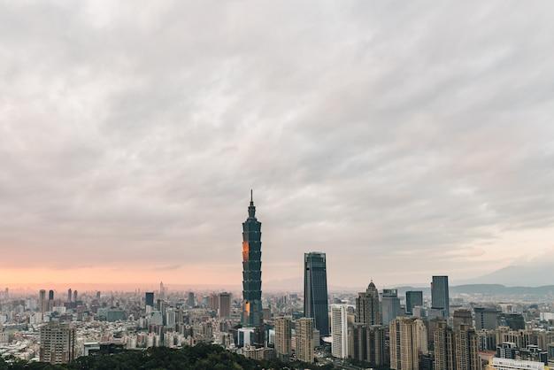 Antenne über im stadtzentrum gelegenem taipeh mit wolkenkratzer taipehs 101 in der dämmerung.