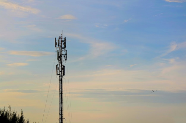 Antennenturmgebäude mit dem blauen, orange himmel und der weißen wolke.