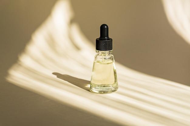 Anti-aging-serum in glasflasche mit tropfer an beiger wand. gesichtsflüssigkeit essentiell mit kollagen und peptiden