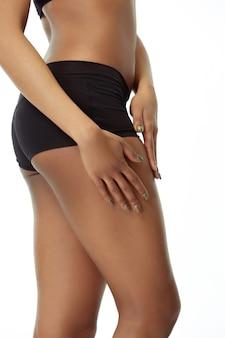 Anti-cellulite. schlank gebräunter frauenkörper lokalisiert auf weißem studiohintergrund. afroamerikanisches weibliches modell mit gepflegter form und haut. schönheit, selbstpflege, gewichtsverlust, fitness, abnehmen konzept.