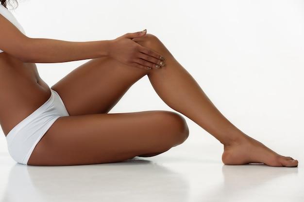 Anti-cellulite und epilation. die beine der schlanken gebräunten frau auf weißem studiohintergrund. afroamerikanisches modell mit gepflegter form und haut. schönheit, selbstpflege, gewichtsverlust, fitness, schlankheitskonzept.