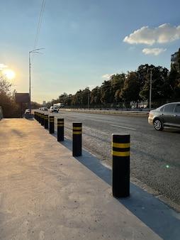 Anti-parkpoller auf dem bürgersteig in der nähe der autostraße unter blauem himmel