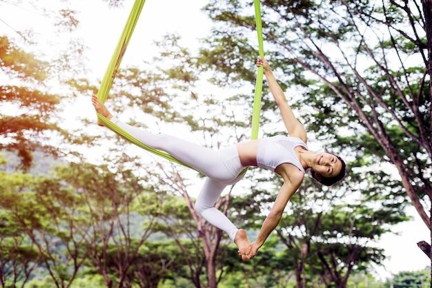 Anti-schwerkraft-yoga oder luft-yoga im freien mit öffentlichem park; akrobatische fliege; pilates und d