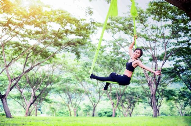 Anti-schwerkraft-yoga oder luft-yoga im freien mit öffentlichem park; akrobatische fliege ..