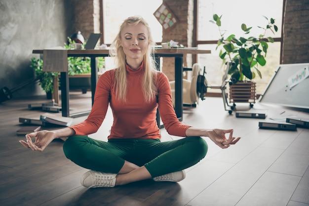 Anti-stress-konzept arbeiten. foto in voller größe von verträumten ceo arbeiter frau haben viele jobprobleme sitzen boden versuchen ruhig üben yoga-übung meditieren in chaotischen großen firmenbüro