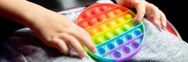 Anti-stress-sensorisches pop-it-spielzeug in kinderhänden. ein kleiner glücklicher junge spielt mit einem einfachen grübchen-spielzeug im auto. kleinkind, das popit-regenbogenfarbe hält und spielt, trend 2021-jahr. banner