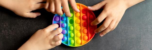 Anti-stress-sensorisches pop-it-spielzeug in kinderhänden. ein kleines glückliches kind spielt mit einem einfachen grübchenspielzeug auf einem schwarzen tisch. kleinkinder, die popit-regenbogenfarbe halten und spielen, trend 2021-jahr. banner