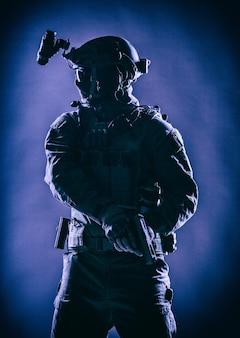 Anti-terroristen-kämpfer, soldat der armee-elite in maske, mit nachtsichtgerät und taktischem funk-headset am helm, bewaffnete dienstpistole, die einsatzbereit steht, zurückhaltendes studio-shooting