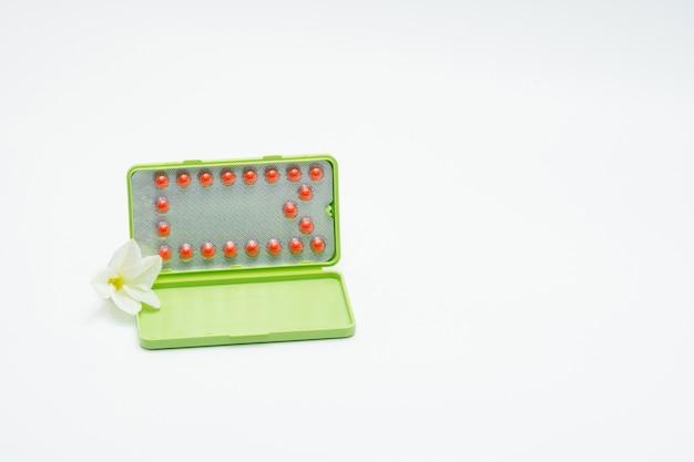 Antibabypillen oder empfängnisverhütende pille mit papierkasten und weißer blume auf weißem hintergrund. familienplanung konzept. hormonersatztherapie. hormonelle aknebehandlung mit antiandrogener pille.