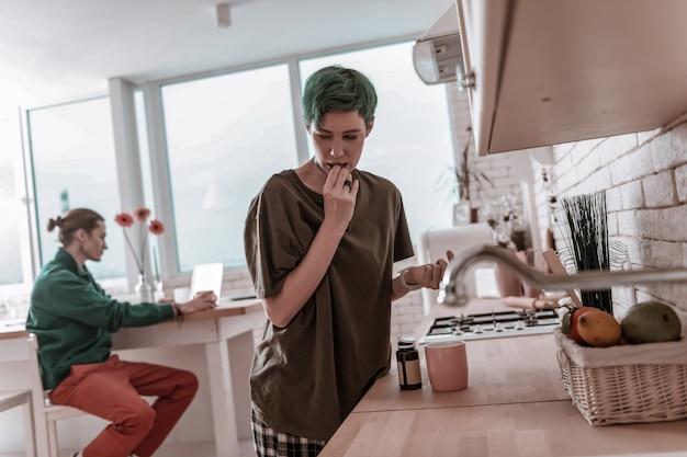 Antidepressiva trinken. grünhaarige frau, die antidepressiva trinkt, während sie an depressionen leidet