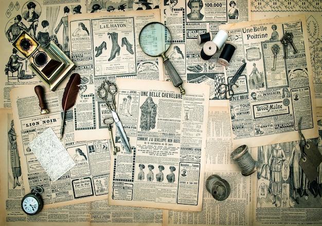 Antike accessoires, näh- und schreibgeräte, vintage-modezeitung für die frau mit werbung. getöntes bild im retro-stil
