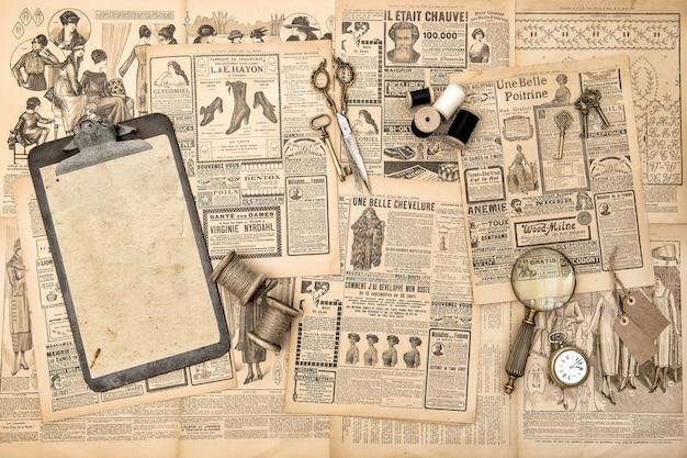 Antike accessoires, nähwerkzeuge, vintage-modemagazin. benutzter papierhintergrund