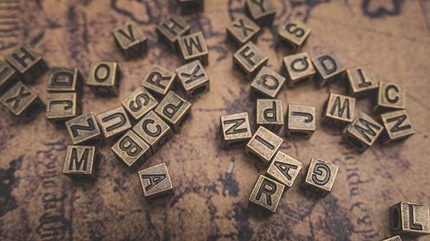 Antike bronze alphabete auf der alten weltkarte