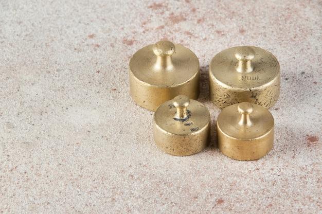 Antike bronzegewichte für waagen auf betontisch.