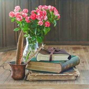 Antike bücherstapel mit rosa blumenstrauß und eine rustikale tasse mit federn liegen auf einem holztisch