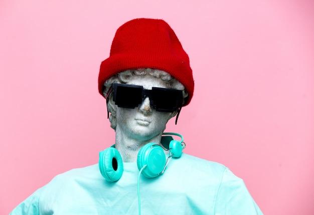 Antike büste des mannes im hut mit kopfhörern und sonnenbrille
