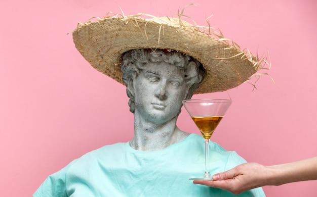Antike büste des mannes im hut mit martini-glas