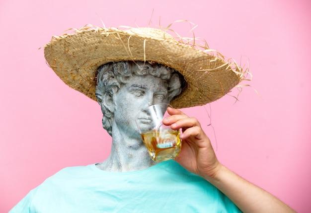 Antike büste des mannes im hut mit whiskyglas