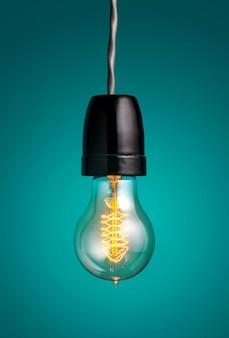 Antike edison-art-fadenglühlampen, die glühlampe über grünem hintergrund hängen.