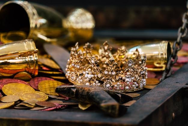 Antike goldschatzkrone mit münzen für reichtum, luxus und erfolgskonzept