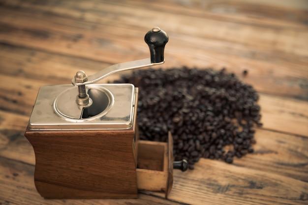 Antike kaffeemühle mit kaffeebohnen hinter