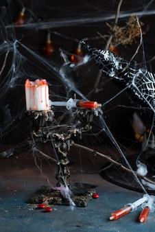 Antike kandelaber mit schmelzender kerze, spinnennetz und einer spritze mit tomatensaft auf schwarzem