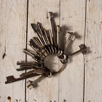 Antike kupferschlüssel auf altem hölzernem hintergrund