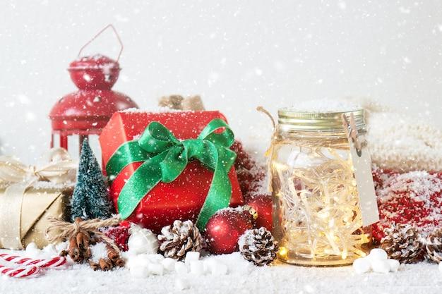 Antike lampe, geschenk-und glas mit lichtern, während es schneit