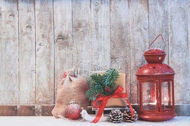 Antike lampe mit einem geschenk an die seite und tannenzapfen