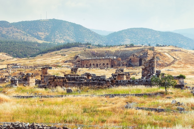 Antike ruinen des griechischen kurortes hierapolis in einer bergigen türkischen landschaft mit dem theater und amphitheater im hintergrund