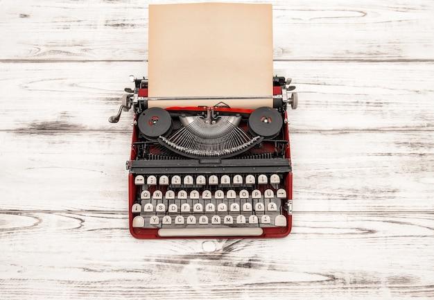 Antike schreibmaschine mit grungy strukturierter papierseite auf holztisch. stillleben im vintage-stil. deutscher schriftzug