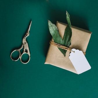 Antike silberschere; eingewickeltes geschenk mit blättern und tag auf grünem hintergrund