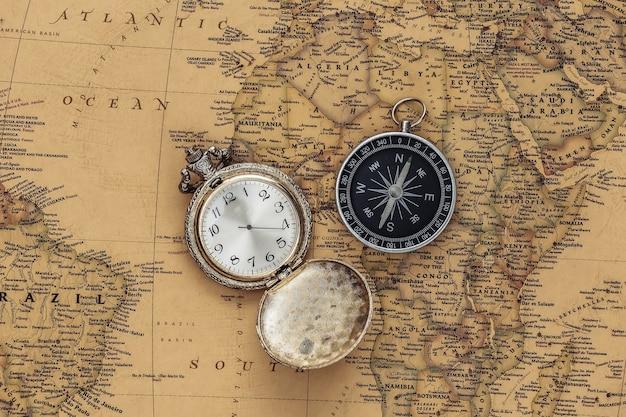 Antike taschenuhr und kompass auf alter karte. reise, abenteuerkonzept