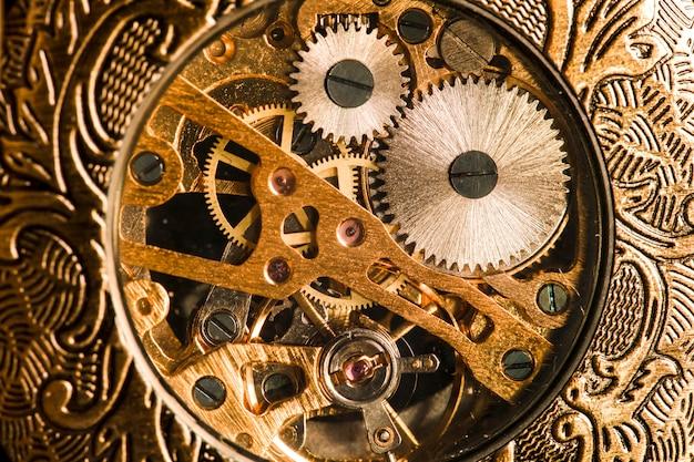 Antike uhr auf dem hintergrund von weinlesebüchern. mechanisches uhrwerk an einer kette.