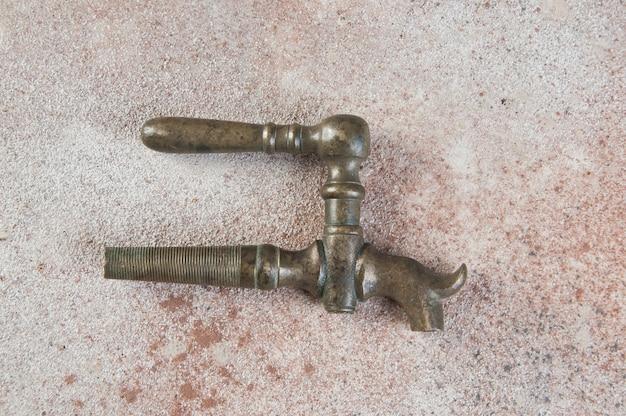 Antiker bronze weinfasskran auf beton