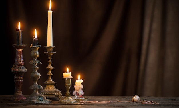 Antiker kerzenhalter mit brennender kerze auf altem holztisch auf hintergrund brauner samtvorhang