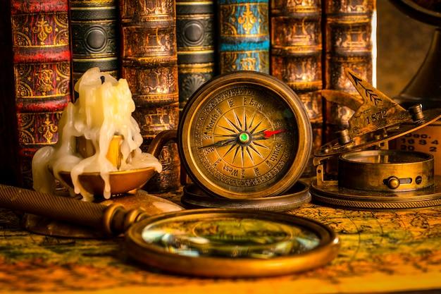 Antiker kompass auf dem hintergrund der lupe und der bücher. vintage-stil. 1565 alte karte des jahres.