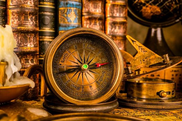 Antiker kompass auf dem hintergrund des globus und der bücher. vintage-stil.
