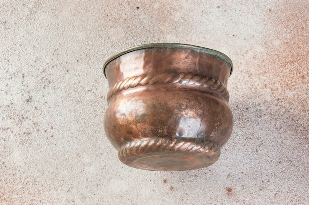 Antiker kupferblumentopf auf betonboden