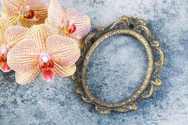Antiker messingbilderrahmen und orchideenblumen
