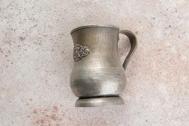 Antiker metallbecher auf einem konkreten hintergrund. kopieren sie platz für text.