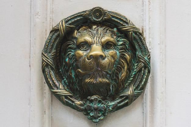 Antiker türklopfer aus bronze, der einen löwenkopf darstellt