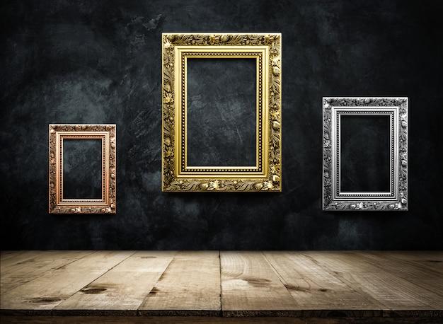 Antikes bilderrahmenkupfer, silber, gold auf dunkler schmutzwand mit holztischoberseite