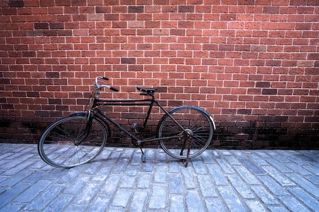 Antikes fahrrad mit hintergrund des roten backsteins. vintage-konzept
