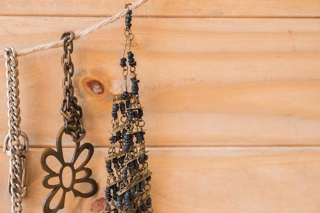 Antikes metallisches und perlenarmband, das an der jutefaserschnur gegen hölzerne wand hängt
