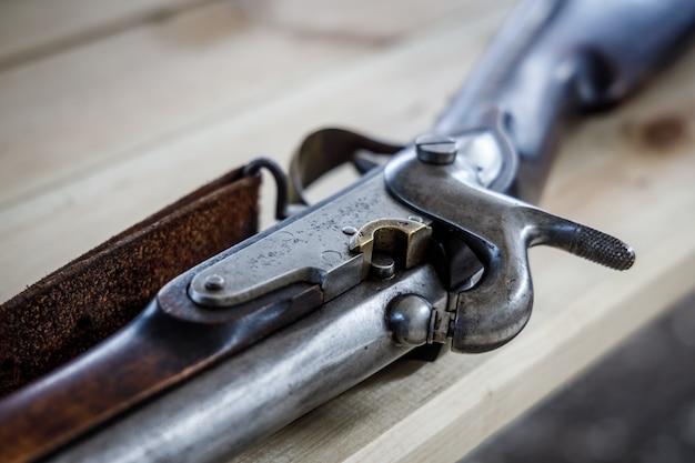 Antikes steinschlossgewehr liegt auf einem holztisch