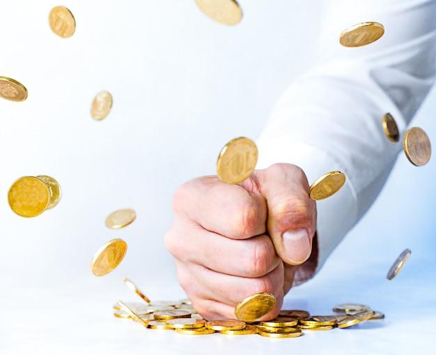 Antikorruptionskonzept. die faust des mannes schlägt auf den tisch und die levitation der goldmünzen. willenskraft gegen reichtum.