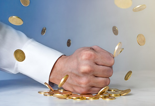 Antikorruptionskonzept. die faust des mannes schlägt auf den tisch und goldmünzen fliegen zur seite. münzen levitation.