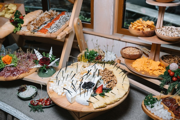 Antipasti-brett mit verschiedenen käse- und fleischsnacks mit hummus und oliven auf rundem holzbrett auf schwarzem tisch
